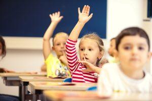 Kinderen met hand omhoog in klas